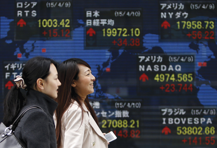 Pedestrians walk past an electronic board showing the stock market indices of various countries outside a brokerage in Tokyo in this file photo taken on April 10, 2015. REUTERS/Yuya Shino