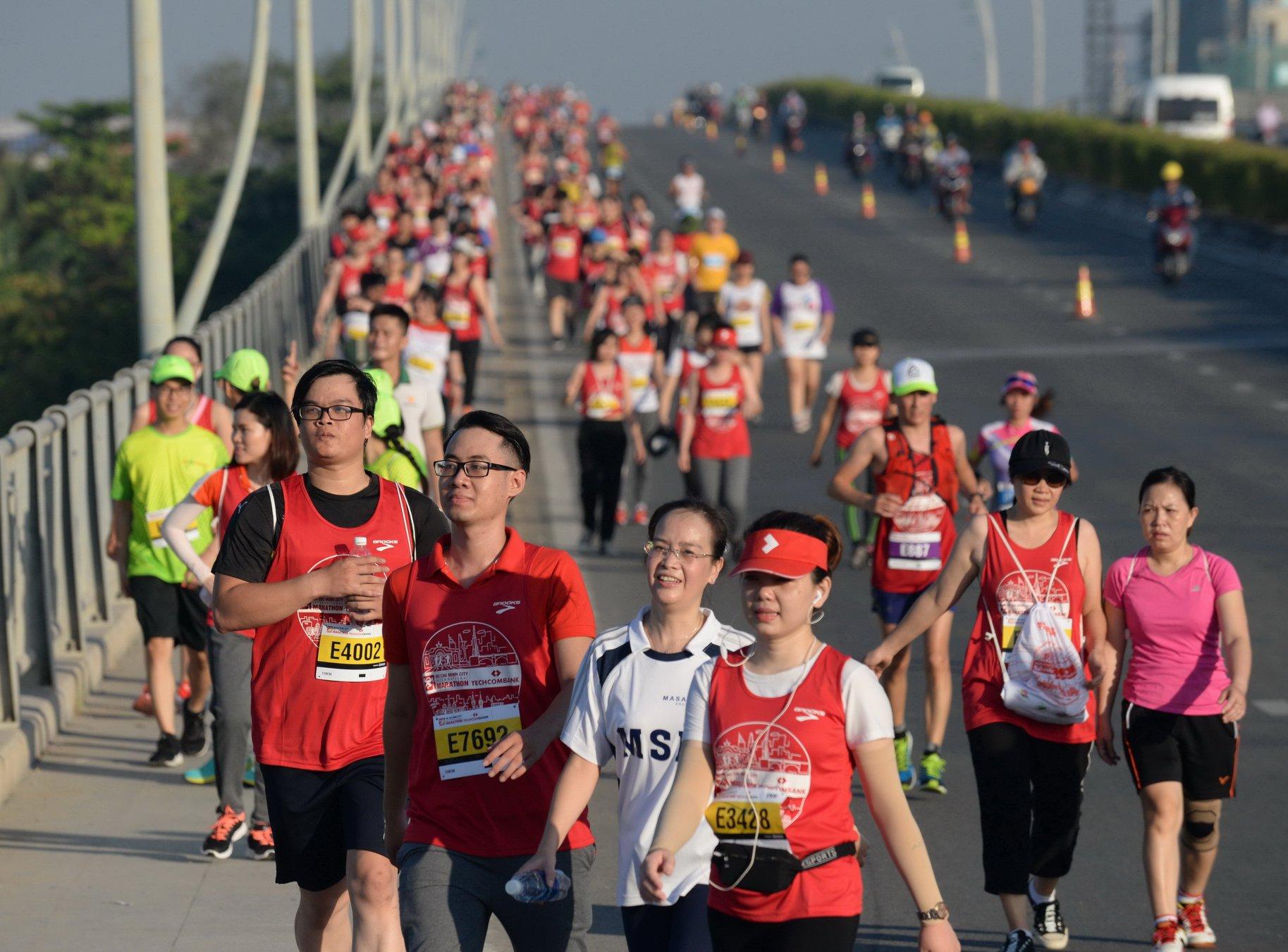 Các vđv đường chạy 10km vừa chạy, đi bộ qua cầu Thủ Thiêm , Q2