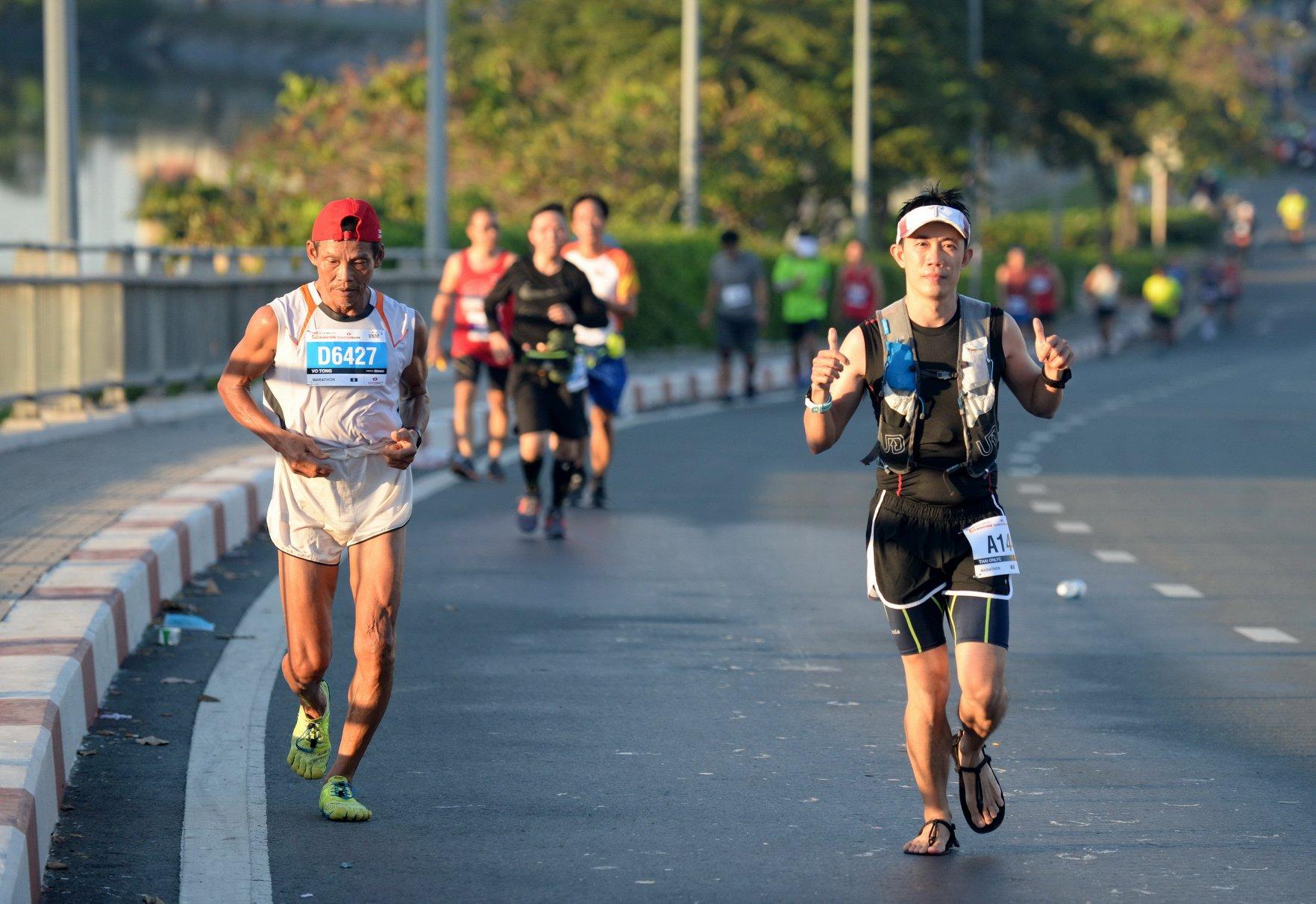 VĐV lớn tuổi Võ Tòng và vđv Thái OnlyC trên đường chạy marathon. | Ảnh: TTD
