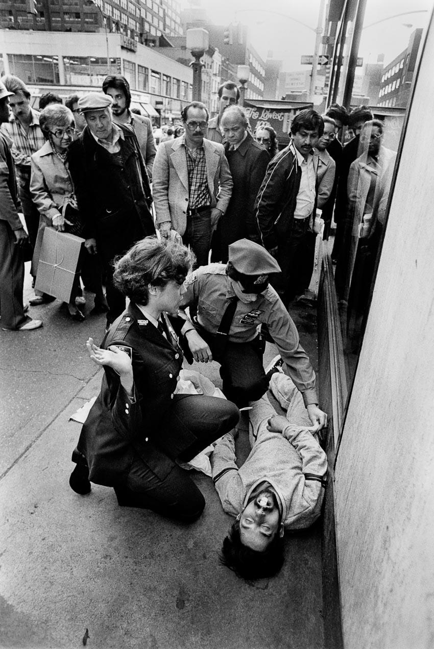 Mọi người tụ tập xem cảnh sát kiểm tra người đàn ông bị sốc thuốc trên phố, 1980