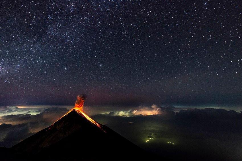 Núi lửa Fuego phun trào vào ban đêm với quang cảnh bầu trời đầy sao ở thành phố Antigua, Guatemala