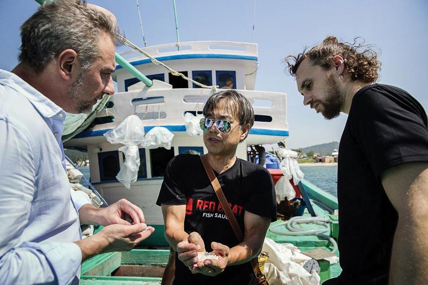 Ông Phạm Cường (giữa) giới thiệu quy trình chế biến nước mắm cho các vị khách quốc tế