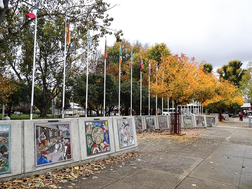 27 lá cờ dọc đại lộ chính của Cooma, chân cột cờ là những bức tranh mô tả thời kỳ đầu xây dựng thị trấn