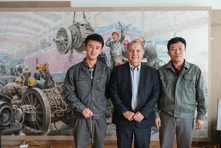 Ông Pier Cecioni với họa sĩ Pak Ouk Chol, 37 tuổi (bên phải) và họa sĩ Kang Un Hyok, 27 tuổi trước một bức tranh họ đang vẽ tại xưởng Mansudae