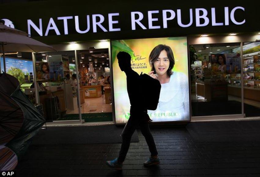 Một thanh niên đi ngang qua chuỗi cửa hiệu bán mỹ phẩm dành cho nam giới ở Seoul