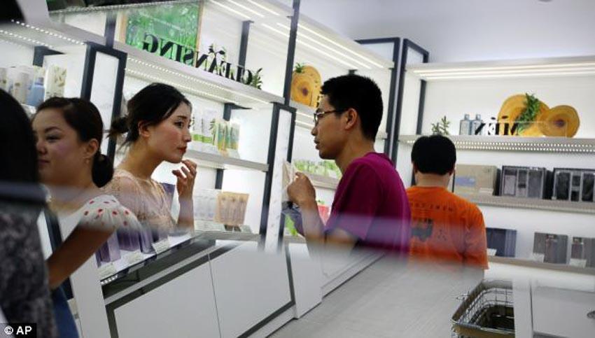 Nữ nhân viên một cửa hàng mỹ phẩm tư vấn sản phẩm cho khách hàng nam giới