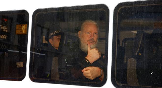 Ông Assange với mái tóc, râu dài bạc phơ ngồi trong xe cảnh sát.@Reuters