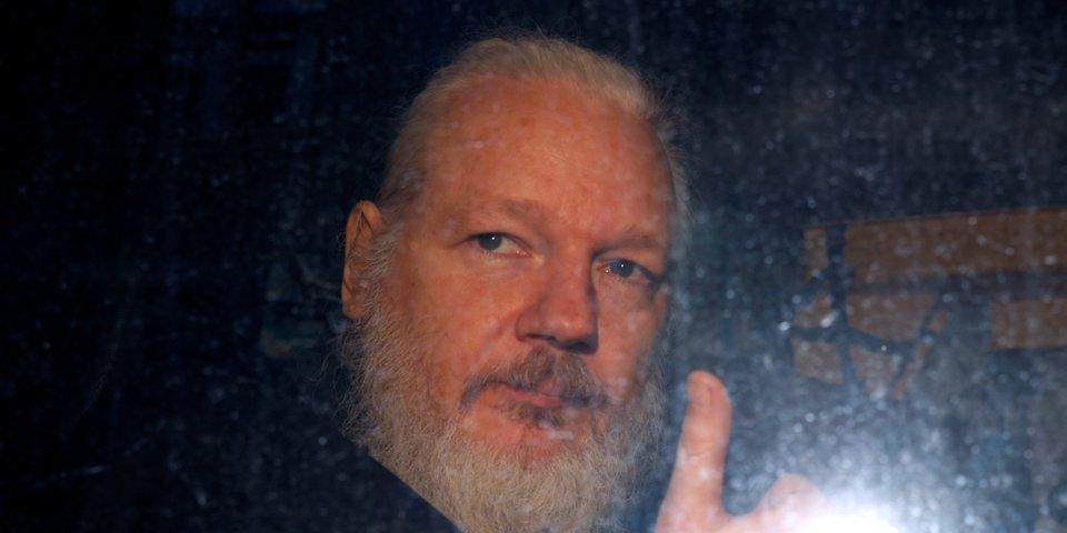Ông Assange với mái tóc, râu dài bạc phơ ngồi trong xe cảnh sát.