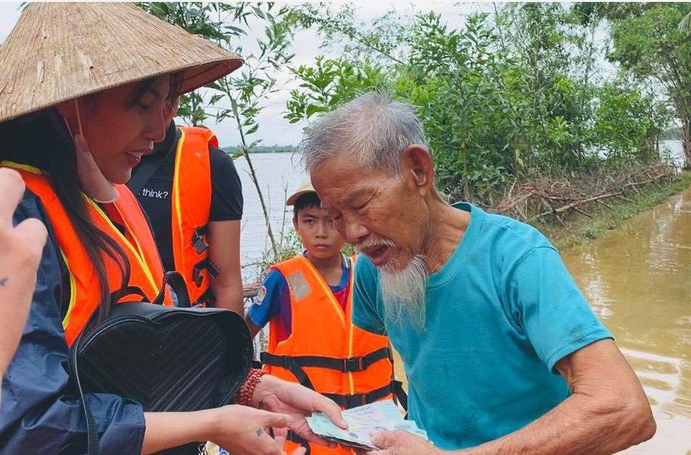 Thủy Tiên trao tiền mặt cho người dân miền Trung bị ảnh hưởng bão lũ. Ảnh: FBNV