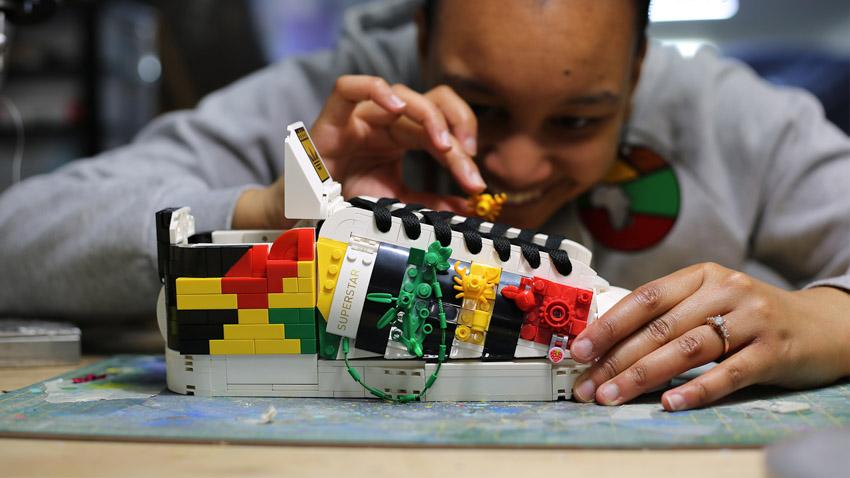 Hình ảnh một người thêm chi tiết vào giày thể thao LEGO adidas Originals Superstar của họ